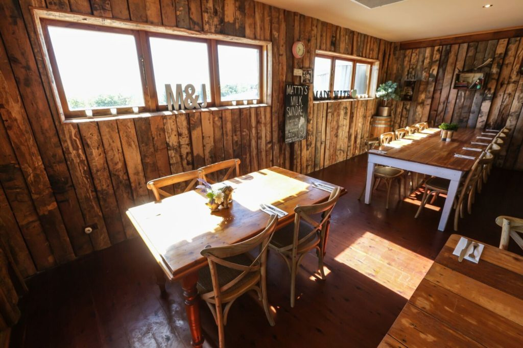 A restaurant room with 6 small windows, a wooden floor and wooden pillars for walls.