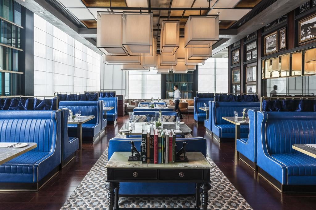 Modern restaurant with bright blue leather banquet seating and square white lighting from the ceiling.