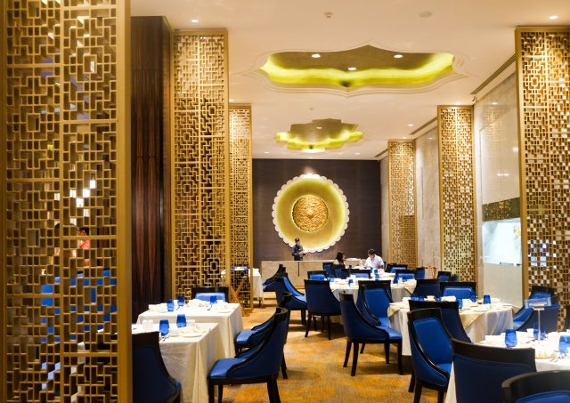 Gold lattice screens with bright blue velvet chairs at tables with white table clothes. Yellow clam shaped lighting.