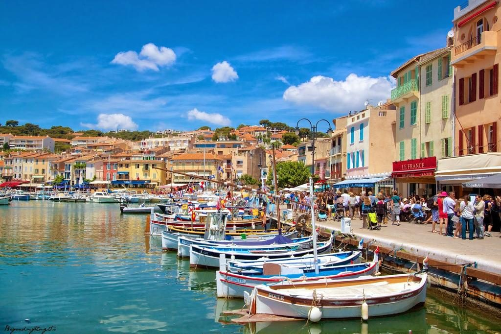 Boats sitting in the ocean next to different coloured French buildings in France.