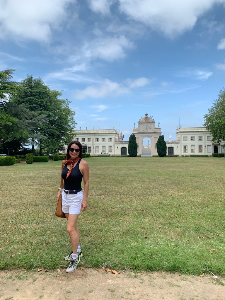 woman in front of large castle and lawns in Portugal