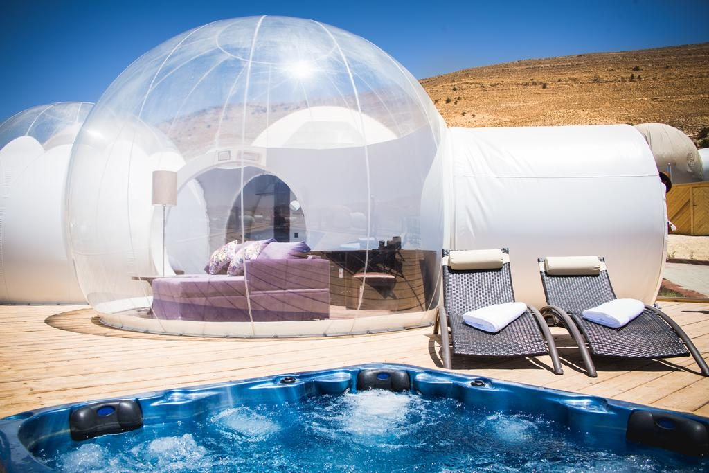 Plastic bubble in desert with  bed inside.