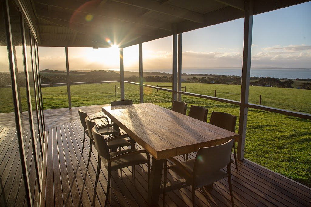 wooden table with 8 chairs drenched in sunlight overlooking grassy area on Kangaroo Island