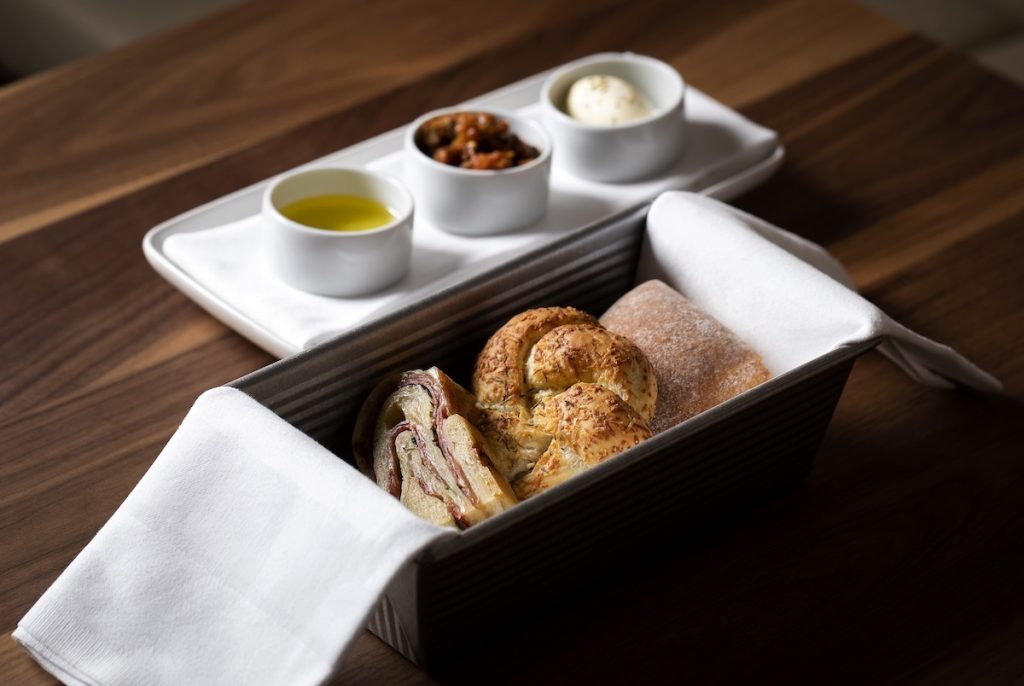 Bread in a metal tin with white napkin, three jars with butter, oil and suace.