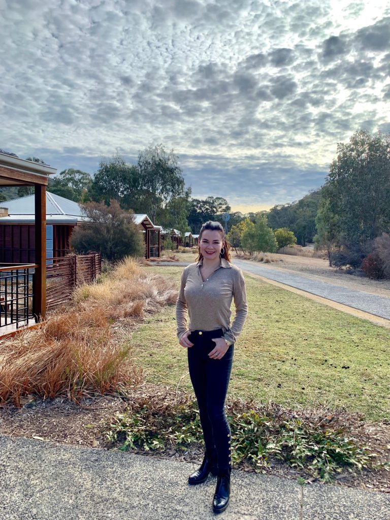 woman in brown jumper and jeans in front of cabin at Emirates One & Only Wolgan Valley Resort