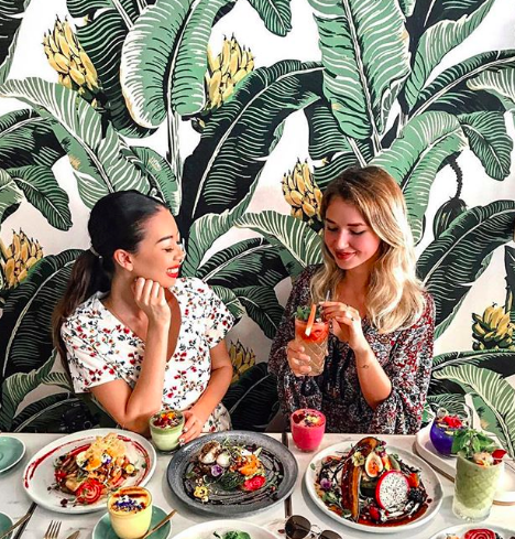 Two girls sat in front of leafy wallpaper.