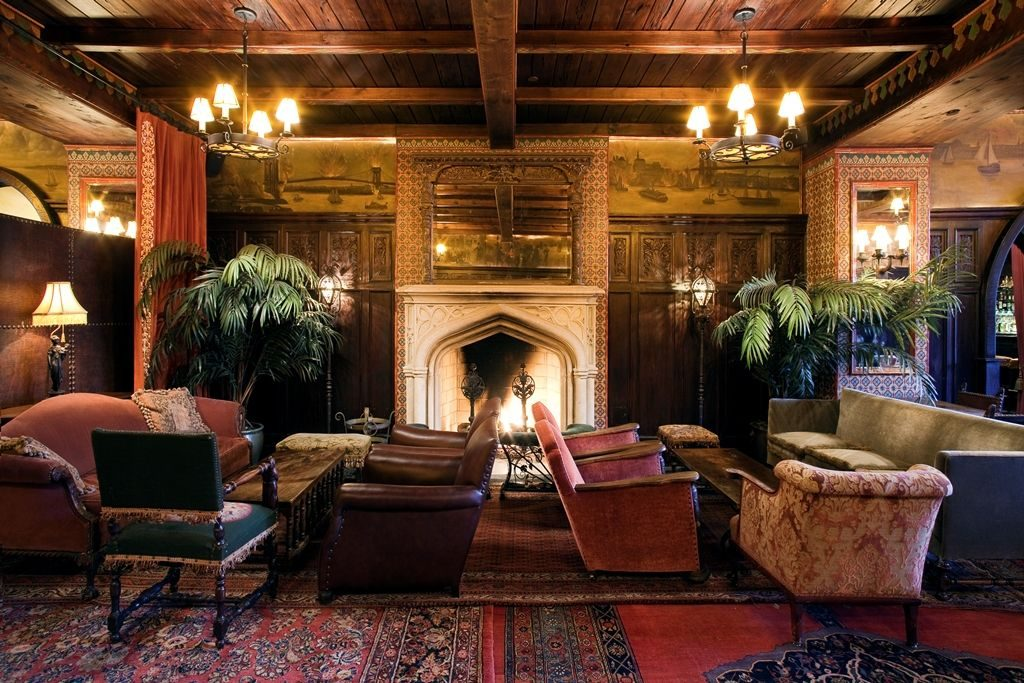 Large room with old style velvet chairs and high ceilings, and a large fireplace.