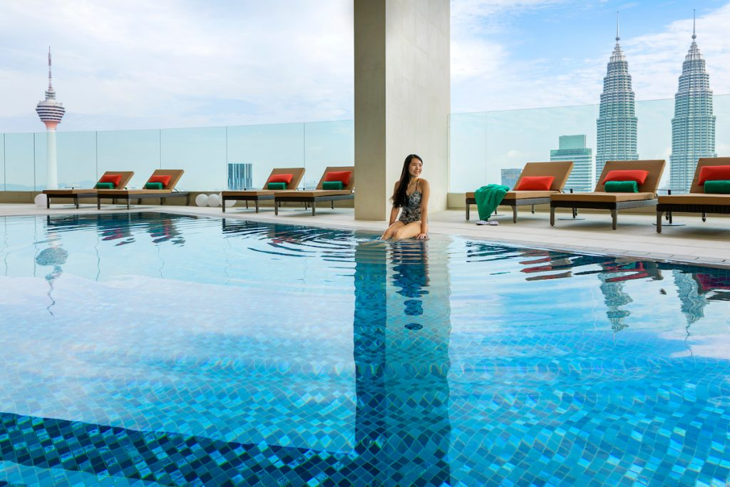 women in hotel pool with Petronas Towers in distance