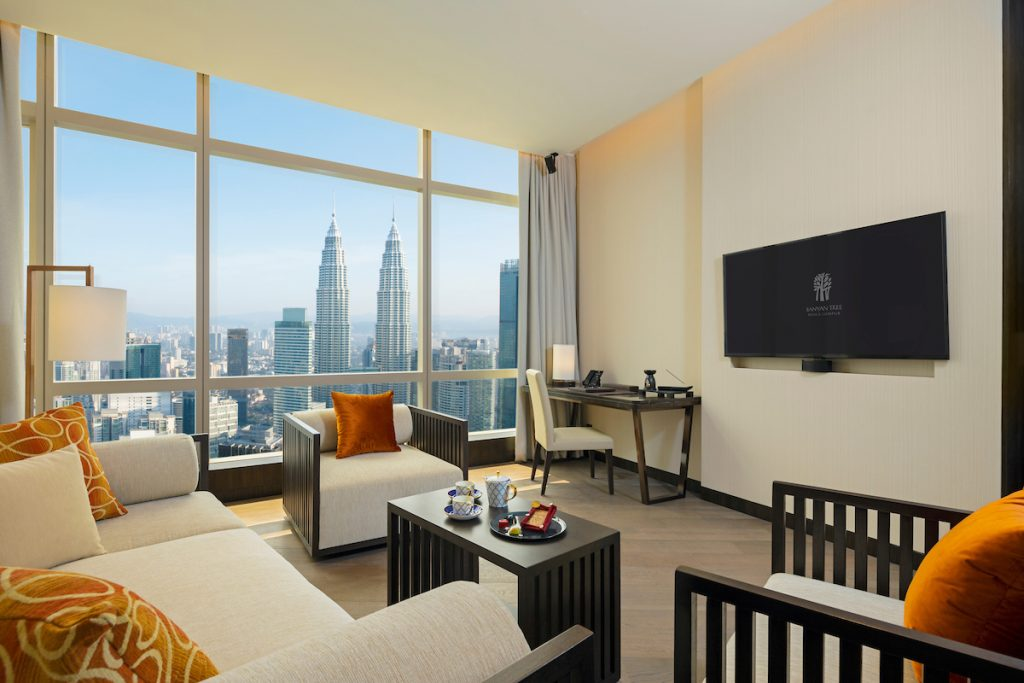 A sprawling hotel room with city views at the end from floor to ceiling windows