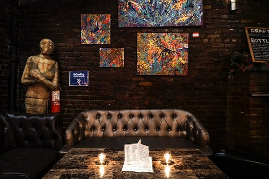 large leather lounge against bacl painetd brick wall with artwork on it.