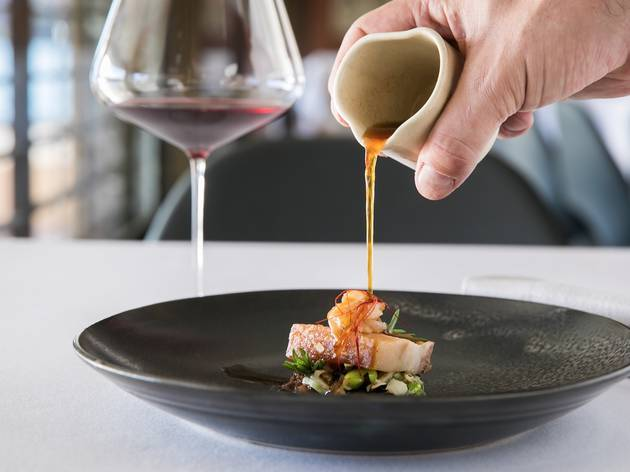 Dish of food with sauce being poured onto it.