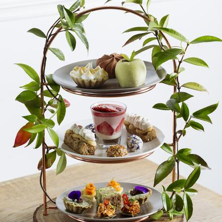 Three tiered high tea trays in a gorgeous stand with plant branches weaved around it