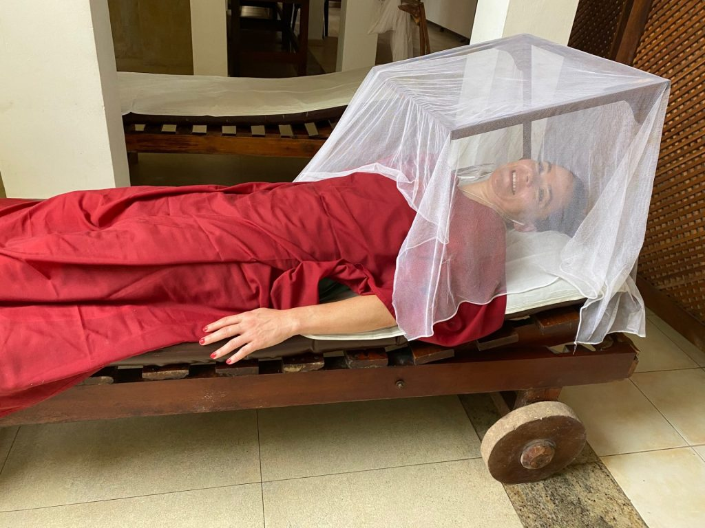 woman with red rug over her and mosquito net in box over her head having a weight loss treatment including papaya face mask