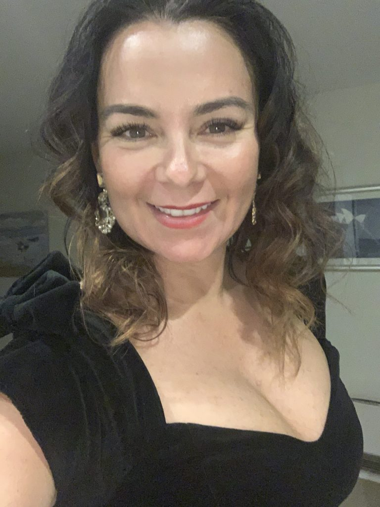 woman with curly brunette hair and plunging black velvet dress
