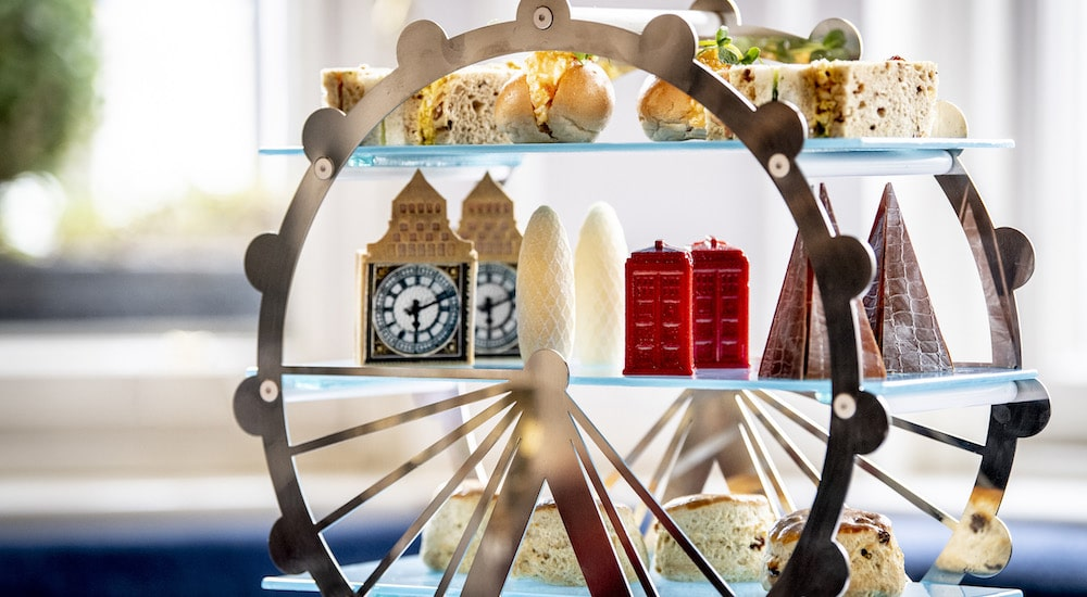 A ferris wheel cake stand holding decadent cakes made out to be symbols of London including red phone boxes, big ben, and so on