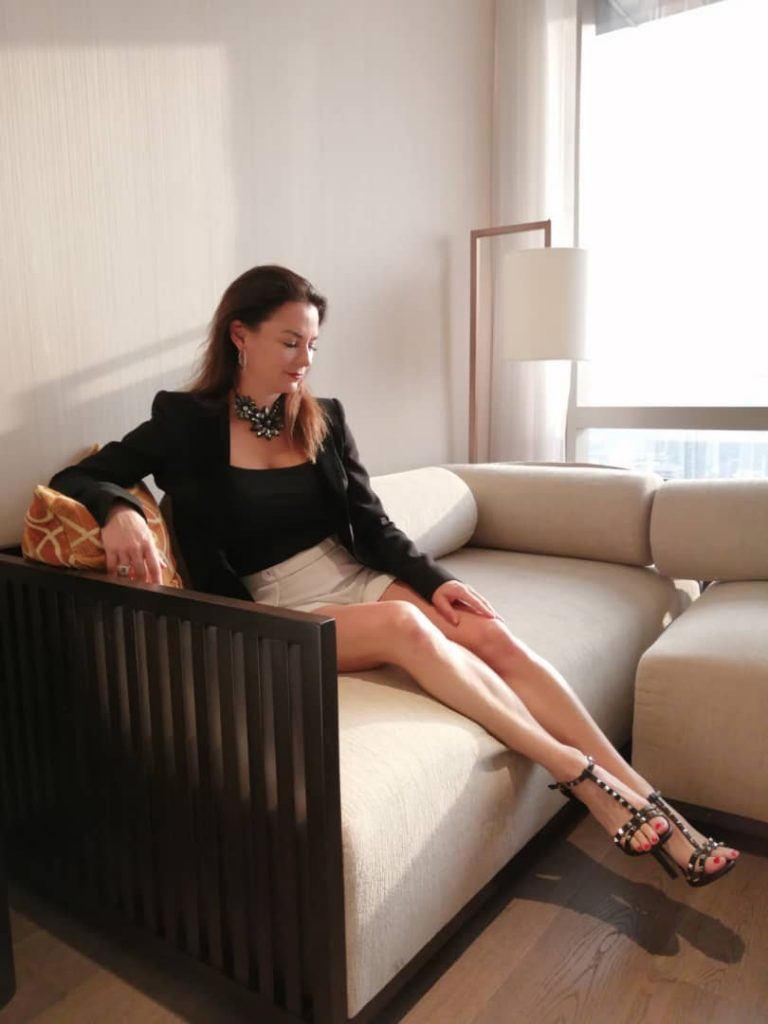 brunette woman in white shorts on couch in hotel toom