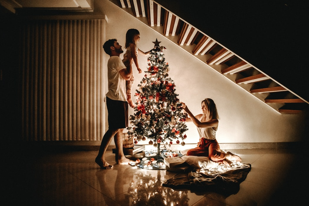 man lifting child next to christmas tree and women on floor putting decorations on tree