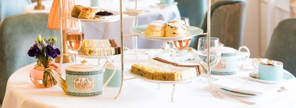 Beautiful high tea setting on a white tablecloth with pale blue chairs around it.