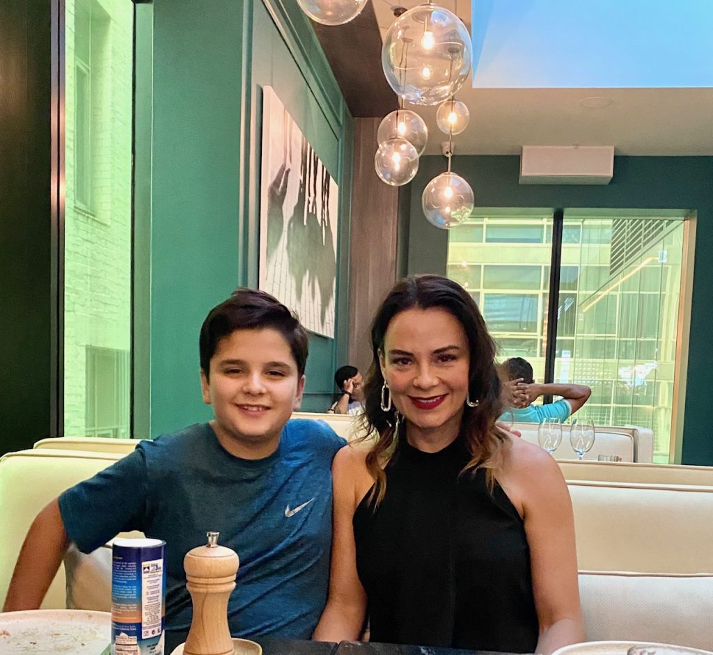 Brunett mother in black top and son in blue top at a restaurant with green walls
