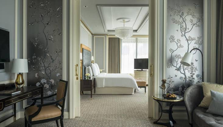 luxe hotel room with silver wallpaper and a large bed