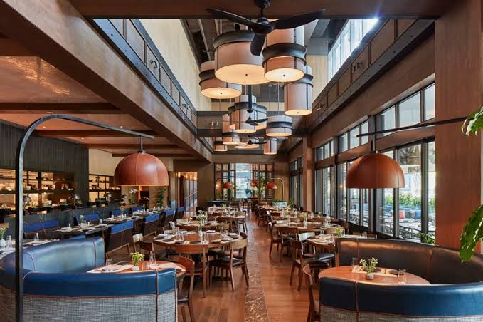large upscale restaurant  with blue chiars, wooden floors and high ceilings