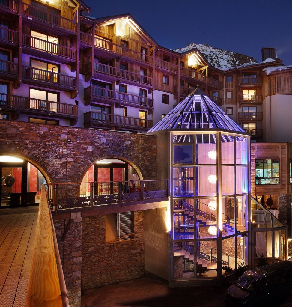 Alpine hotel at night lit up inside with a clear glass lift
