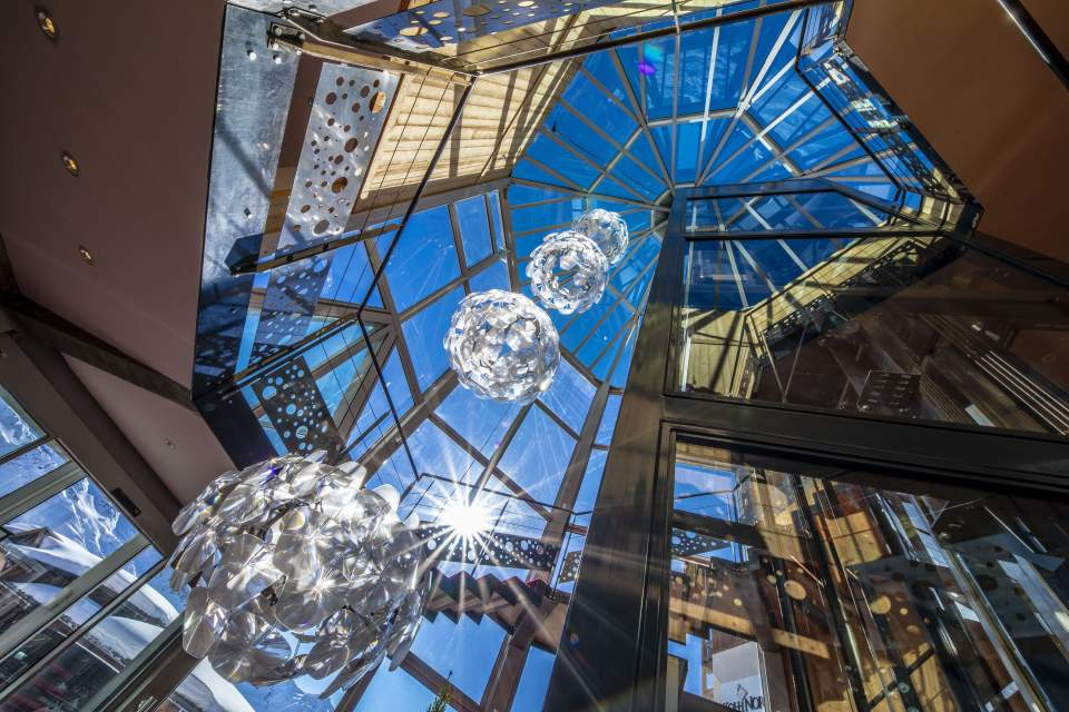 Looking up through a glass atrium, with circular ball light fittings in front of a bleu sky