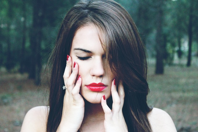 women with red lips, dark hair and pale skin and red nails