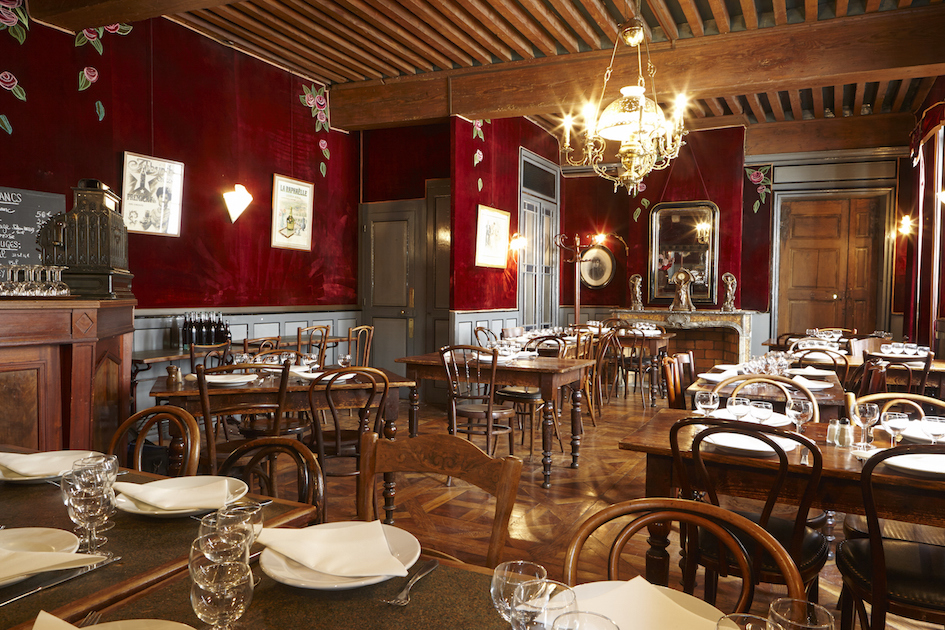FRENCH RESTAURANT WITH DEEP RED WALLS, BROWN WOODEN FLOORS AND SMALL ROUND WOODEN TABLES AND CHAIRS