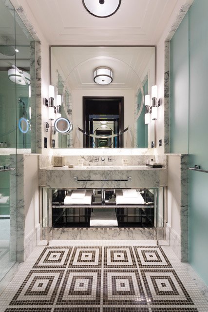 Moasic black and white tiles on bathroom floor with large square mirror and sinks