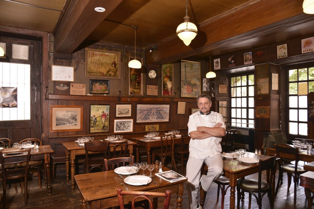 chef in white in an old style wooden walls, ceiling and floor restaurant with brown wooden tables and coloured small art works in the wall behind him