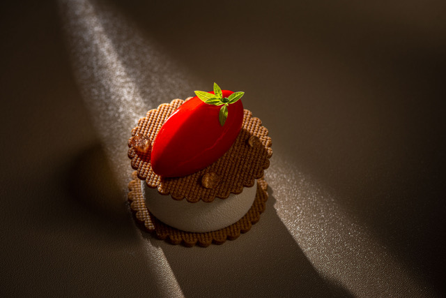 Gorgeous strawberry atop a brown biscuit with white cream on the middle