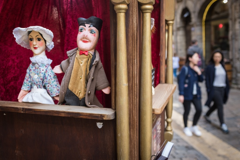 Puppets on a shelf with tourists walking by in France