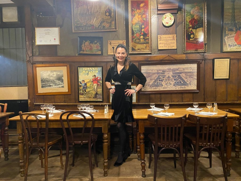 Brunette woman in bistro style restaurant with painting on wall behind and wooden tables and chairs