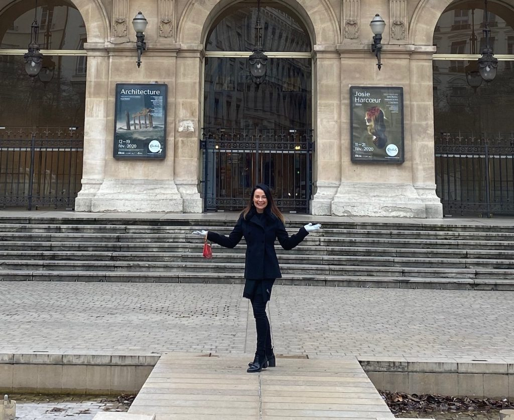 woman standing in front of grand old building  with 10 steps out front in Lyon, France