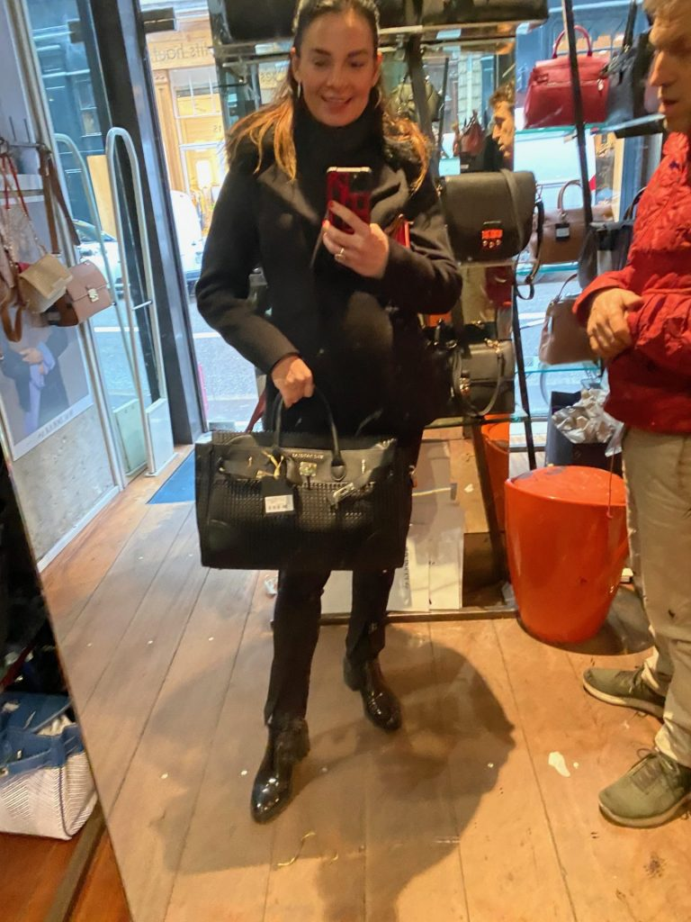 woman shopping in handbag shop with bag in front