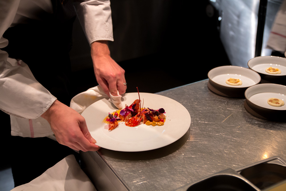 Chef cleaning a white round plate with red food on it