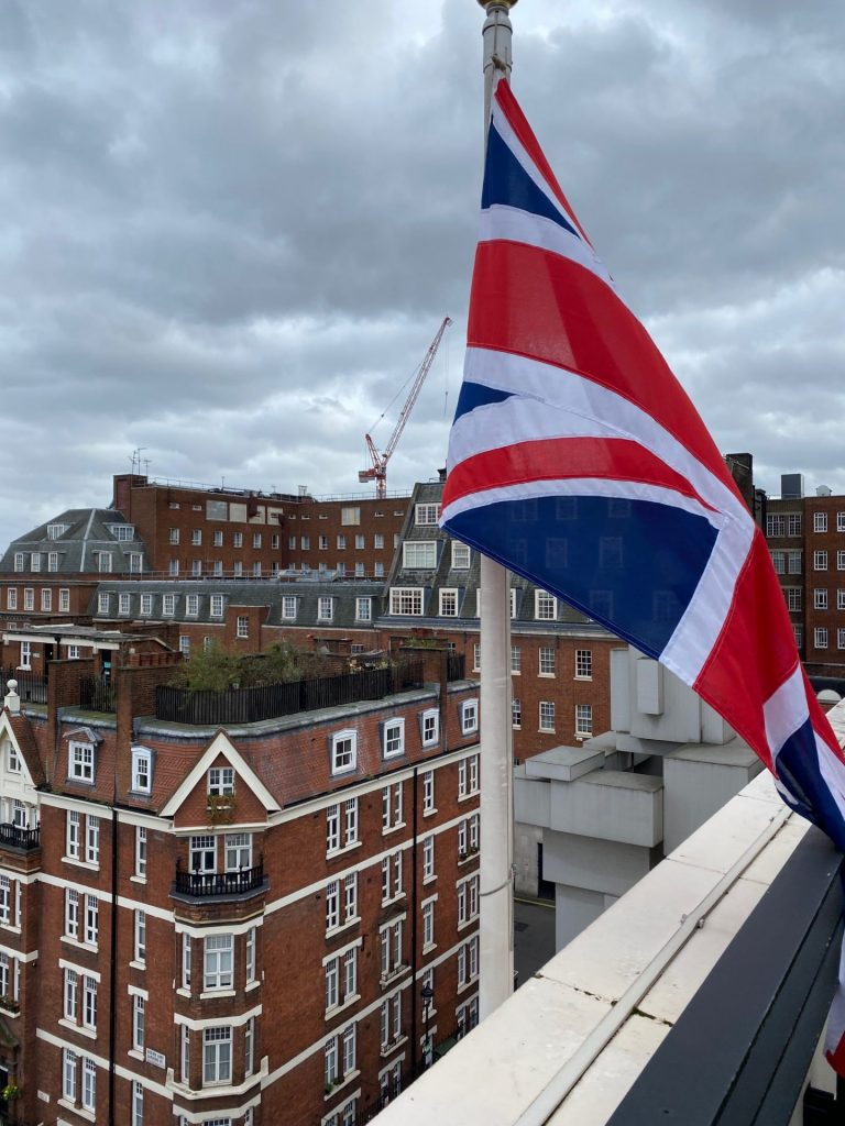 UK flag flying in front of british building in Mayfair