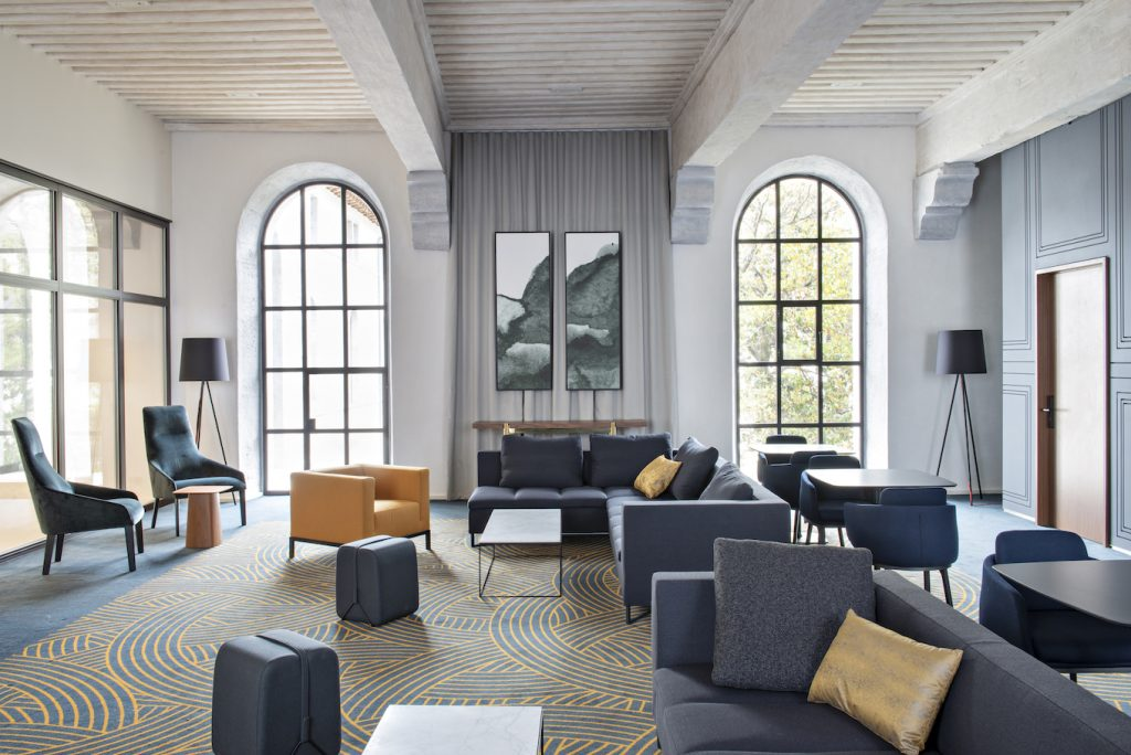 Huge living room in five star hotel with two acrhed windows letting in natural light, white ceilings and grey floors and furniture