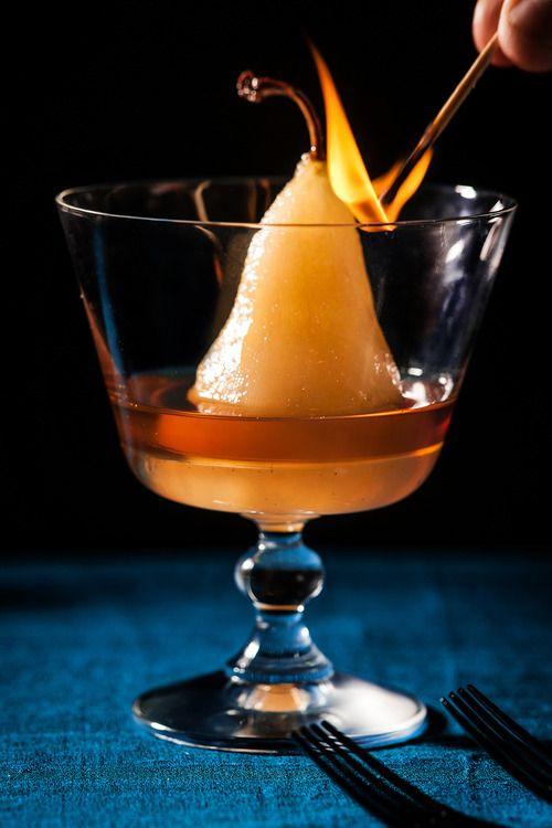 small skinless apricot coloured pear in a large gas with liquid in the bottom and a match with a flame at the top