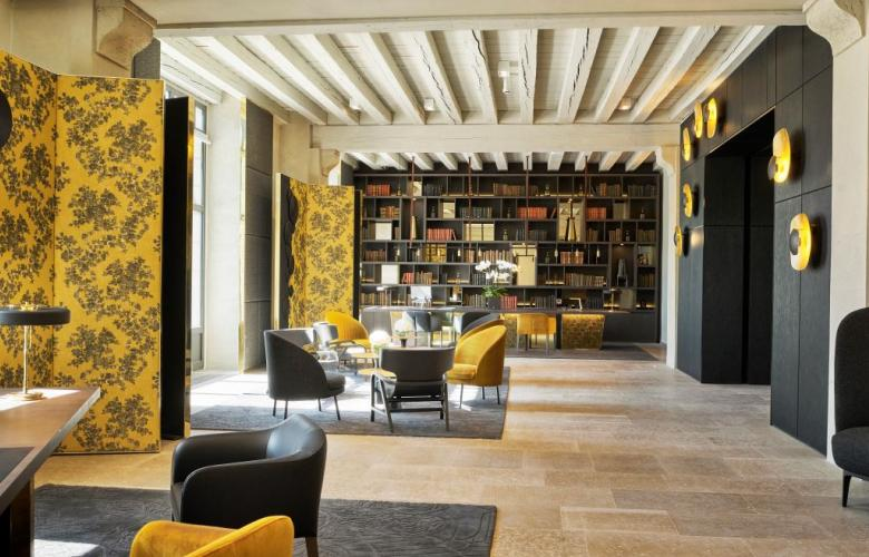 White slatted ceilings in a large lobby with yellow wall paper walls in a hotel lobby in france