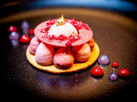 pastry base, pink meringue mounds topped with a pink plate and white dessert in the middle