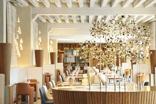 gold art feature in the light at the entrance of a restaurant with white slatted wooden ceilings