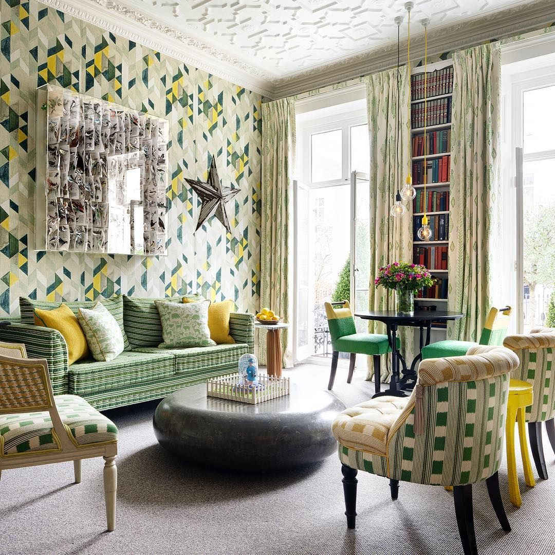 Colourful room with green and yellow wallpaper, large windwos with doors open, grey carpet and colourful chairs.