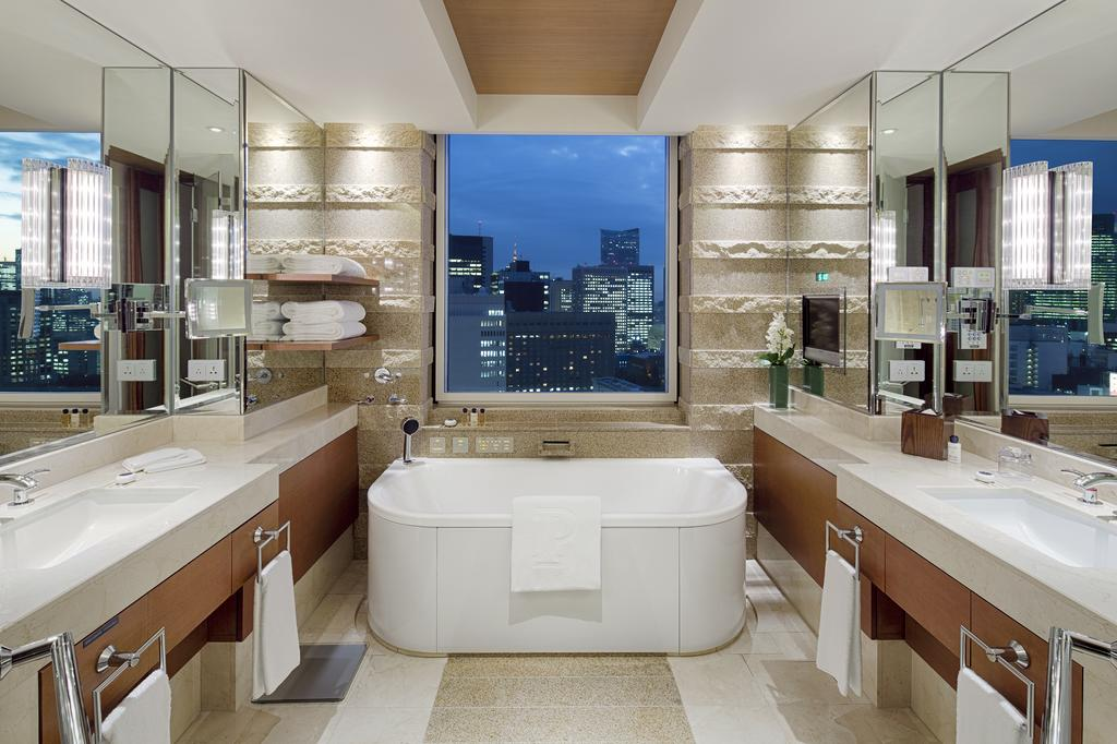spa bath at the end of hotel room with benches on each side and window at the end overlooking skyscrapers