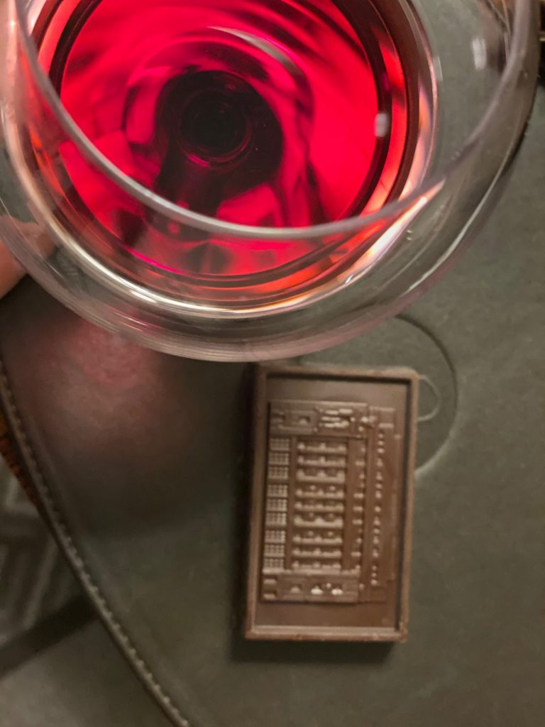 red wine glass with block of dark chocolate next to it.