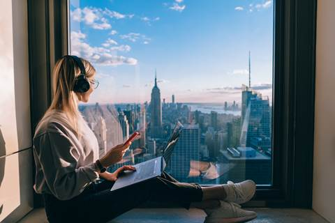 woman with headphones looking out over window to new york rooftops and skyline