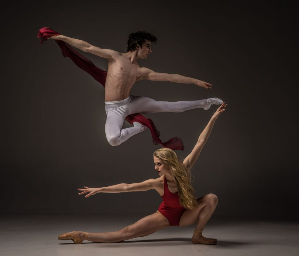 male dancer in white pants and blonde woman in red leotard dancing and jumping together