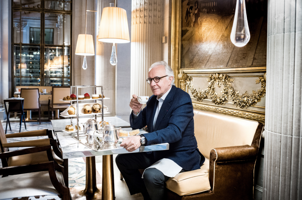 Alain Ducasse in navy suit dining, facing the camera