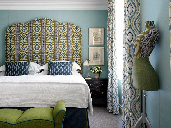 Beautiful hotel room with colourful blue and yellow bed head, white sheets, blue cusions, green sette at end and mixed xolour curtains.